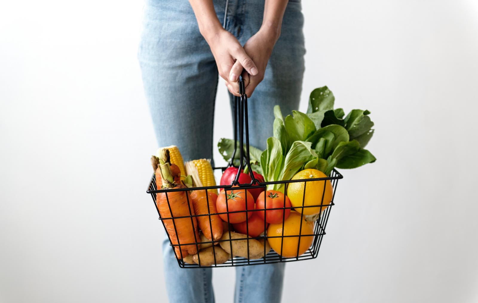 Woman holding a basket of food. Photo credit: Pexels