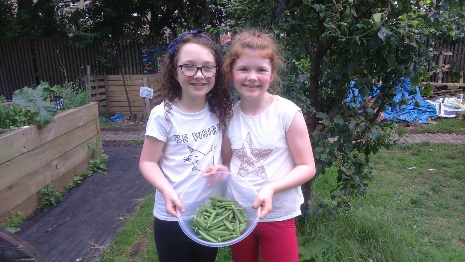 Two Glasgow residents enjoying locally grown veg. Credit: Glasgow Community Food Network